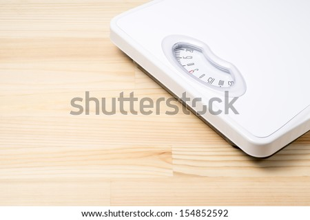 Analog weight scale on wooden floor - stock photo