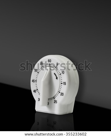 Analog winding white kitchen cooking timer in studio. - stock photo