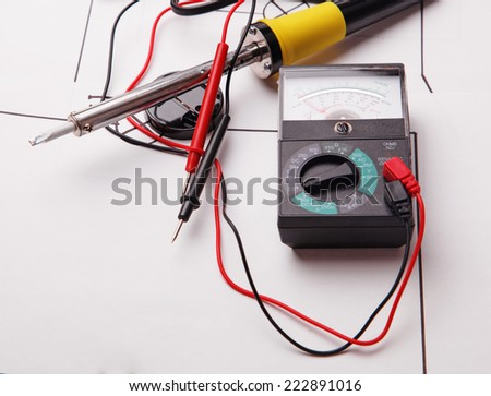 Analogue multimeter with probe and on a background of the electric scheme  - stock photo