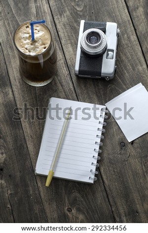 Analogue photo camera on a table with coffee and paper notes - stock photo