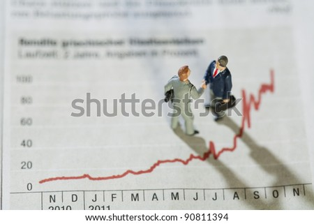 Analysing Annual Monthly Statistics. Two miniature figurines of businessmen having a meeting alongside a fluctuating red line graph showing improving performance over the year.