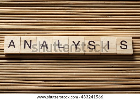 Analysis text on a wooden cube at wood background.