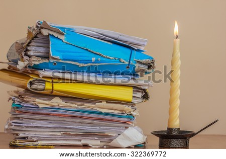 analyze a stack of documents and folders un the light of  a candle - stock photo