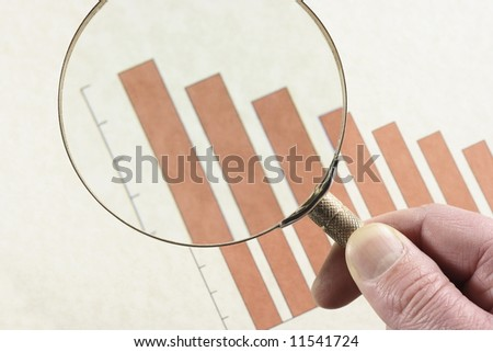 Analyzing a downward trend on a bar graph with a magnifying glass. - stock photo