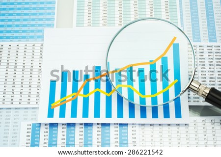 Analyzing data. Checking graph with magnifying glass. Many charts, graph and magnifying glass.  - stock photo
