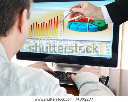 Analyzing  financial data and charts on computer screen. - stock photo