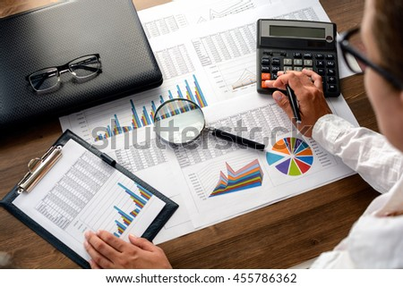 Analyzing financial data and counting on calculator. - stock photo