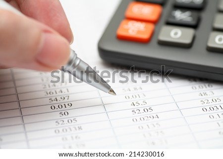 Analyzing financial statements. Focus on ballpoint pen. Shallow depth of field. Close-up. - stock photo