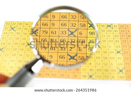 Analyzing lottery ticket with magnifier, closeup