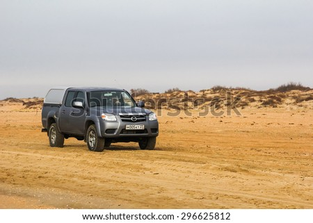 ANAPA, RUSSIA - NOVEMBER 19, 2014: Off-road pickup truck Mazda BT-50 at the sandy beach. - stock photo