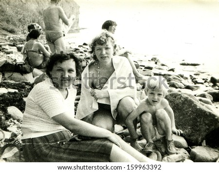 ANAPA - 1986: two young women and little boy seating on the bank of Black Sea, Anapa, Krasnodar Kraj, Russia, 1986. Name of boy is Victor, 5 years old.