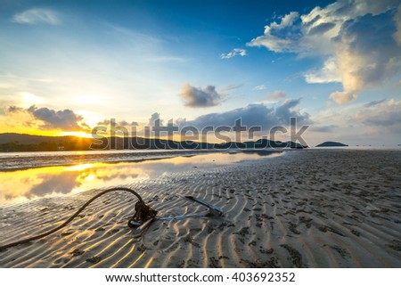 anchor on the tropical beach with sunrise an reflection in water