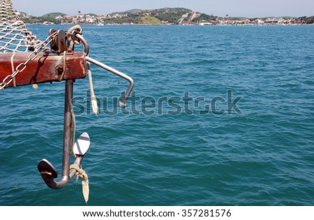 Anchor on vintage wooden sailing ship on blue tropical ocean  View at green mountains in caribbean sea in tourist hotspot Buzios Brazil sailing on a sunny day in summer - stock photo