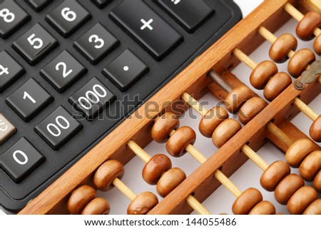 Ancient abacus and modern calculator - stock photo