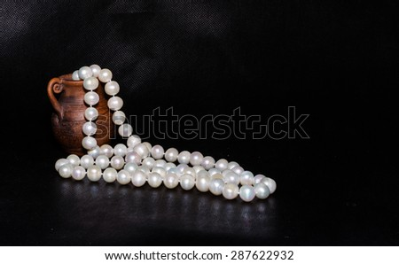 Ancient amphora and pearls over black - stock photo