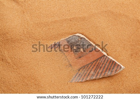 ancient Anasazi pottery shard buried in red desert sand - stock photo