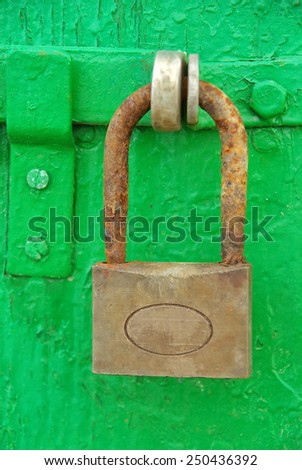 Ancient and rusty iron padlock on a wooden green door - stock photo
