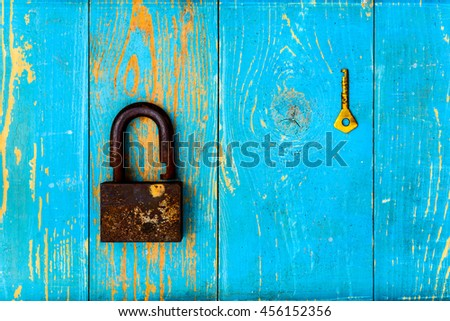 Ancient and rusty open padlock with key on old wooden table covered with blue paint. View from above