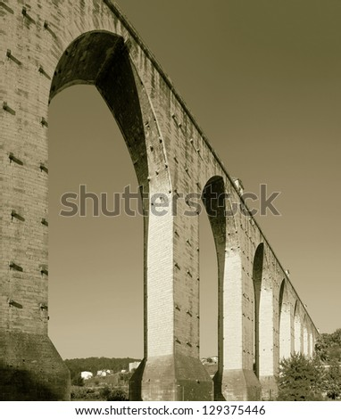 ancient aqueduct in the Lisbon built in 18th century, Portugal (stylized retro) - stock photo