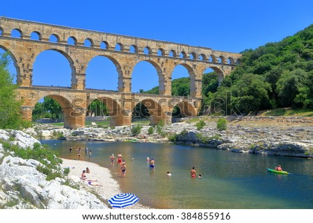 Ancient arches of Pont du Gard and people swimming on the river near Nimes, France - stock photo