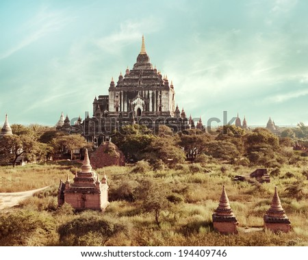 Ancient architecture of old Buddhist Temples at Bagan Kingdom, Myanmar (Burma). White Thatbyinnyu Temple is one of the biggest in Bagan. Travel landscapes and destinations in vintage style.  - stock photo