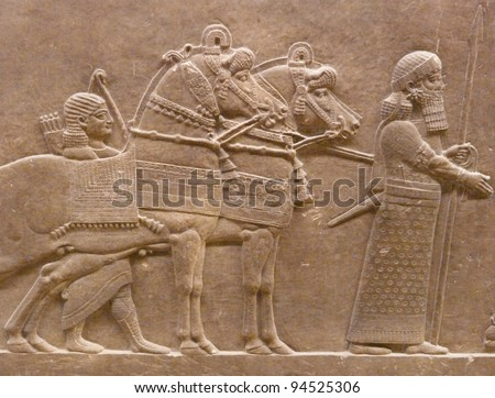 Ancient Assyrian wall carvings of men and horses - stock photo
