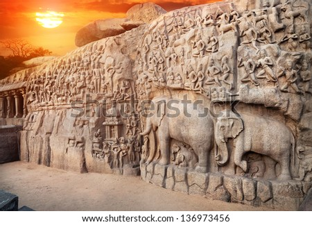 Ancient basrelief of Elephants and another hindu deities at sunset sky in Mamallapuram, Tamil Nadu, India - stock photo
