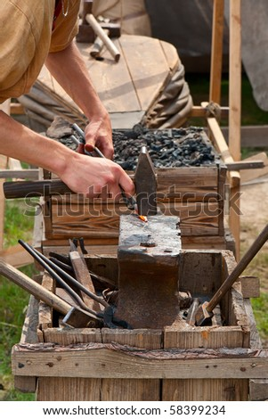 Ancient black smith craftsman working with steel