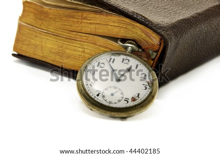 ancient book with a pocket watch isolated on a white background