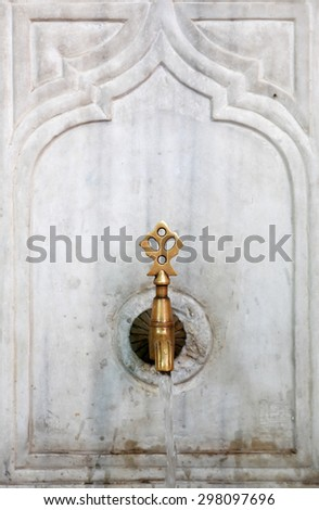 Ancient bronze faucet with flowing water for traditional islam ablution
