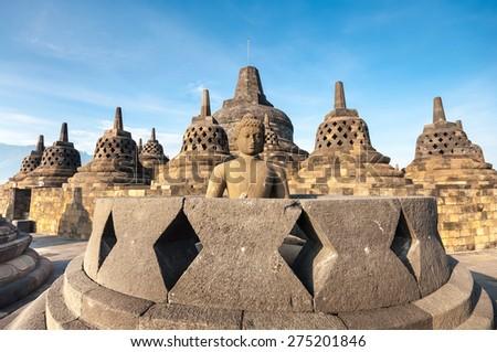 Ancient Buddha statue and stupa at Borobudur temple in Yogyakarta, Java, Indonesia.  - stock photo