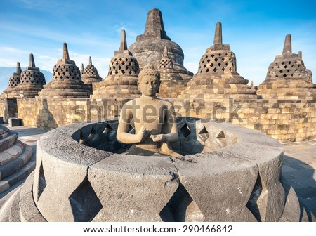 Ancient Buddha statue and stupa at Borobudur temple in Yogyakarta, Java, Indonesia.  - stock photo