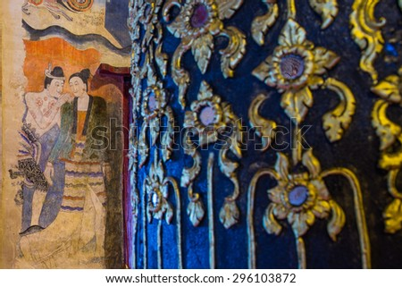 Ancient Buddhist temple the famous mural painting of a man whispering to the ear of a woman. at Wat Phumin, a famous temple in Nan province,Thailand. The temple is open to the public. - stock photo