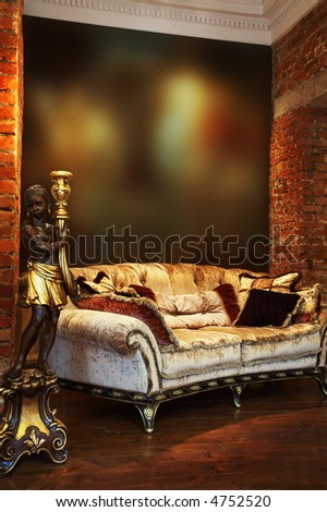 Ancient candlestick and sofa with pillows in an apartment - stock photo