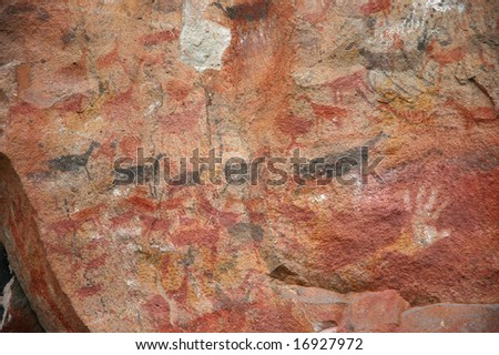 Ancient cave art of Patagonia, human hands next to herds of guanaco. - stock photo