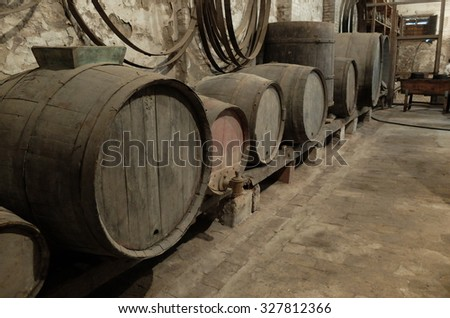 ancient cellar with old bottles and barrels for aging wines from Tuscany Italy spilamberto Modena - stock photo