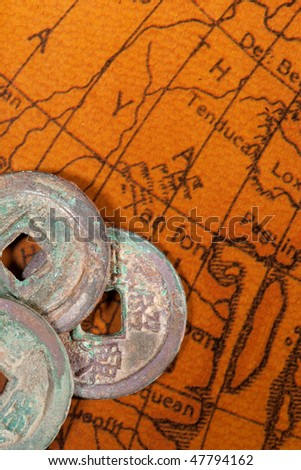 Ancient Chinese coins over antique map