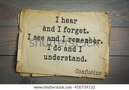 Ancient chinese philosopher Confucius quote on old paper background. I hear and I forget. I see and I remember. I do and I understand.