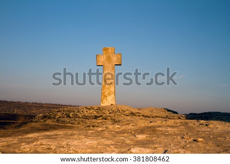 Ancient Christian stone cross on the hill with blurred fields in the background and blue sky, Old Orhei place in Moldova. - stock photo