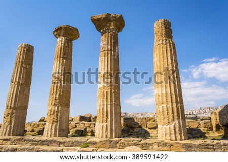 Ancient columns of Hercules Temple at Italy, Sicily, Agrigento. Greek Temples Valley with city background.