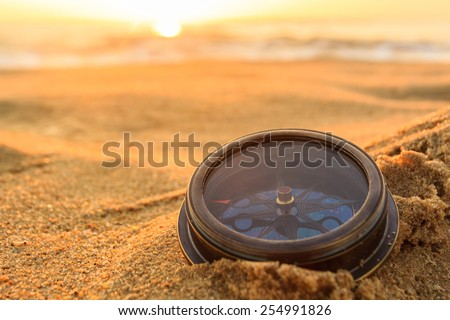 Ancient compass on the sand at the Beach Sunrise ,nature background . - stock photo