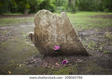 ancient crooked tombstone with room for name on epitaph - stock photo