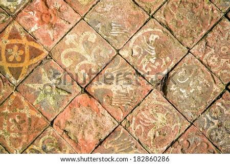 ancient decorative quarry tile floor depicting birds flowers and stars