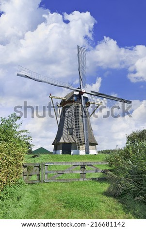 Ancient drainage windmill with thatched roofing in a green meadow with dramatic shaped clouds and a blue sky.