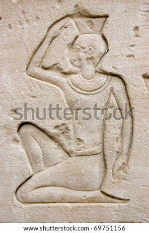 Ancient egyptian carving of someone kneeling before the gods.  Outer wall of the Temple of Horus, Edfu, Egypt. - stock photo