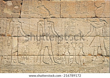 Ancient Egyptian carvings of people and hieroglyphics
