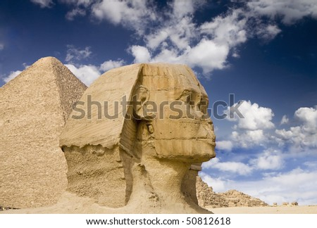 Ancient Egyptian Sphinx with old historic pyramid behind
