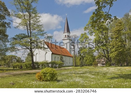 Ancient Evangelic Lutheran church in Sigulda, Latvia among spring green trees