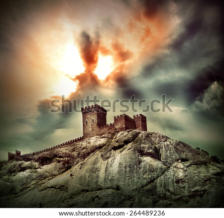 Ancient fortress on the hill under dramatic sky - stock photo