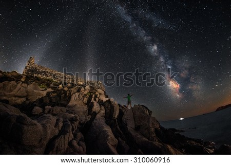 Ancient fortress under a starry night with milky way and a man admiring it - stock photo